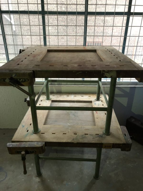 Oude houten vierkante werkbank op industrieel onderstel