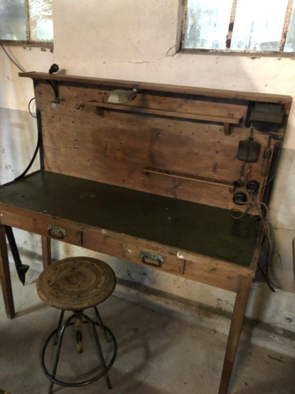 Kleine oude houten werkbank met opstaande wand
