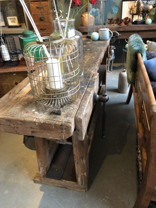 Lange smalle oude houten werkbank met opbergruimte
