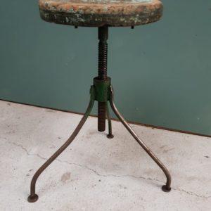 Oude industriele kruk, driepoot met houten zitting