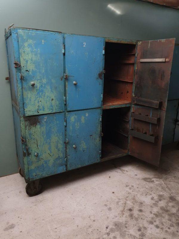 Grote blauwe oude industriele vakkenkast op wielen