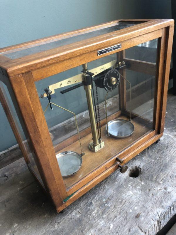 Oude Apotheker weegschaal in vierkante glazen vitrinekast