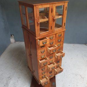 Oude houten hoge ladenkast met glazen deuren