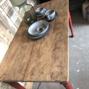 Oude houten tafel met rood onderstel