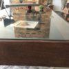 Oude houten vitrinetafel met glazen plaat