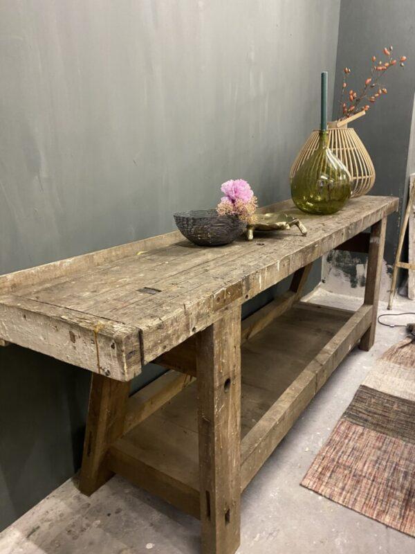Oude lange robuuste houten werkbank met opbergruimte