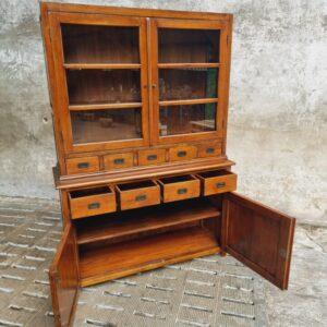 Oude houten eiken kast met glazen deuren en veel laden